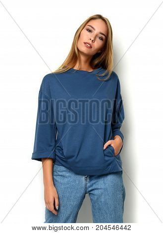 Young happy beautiful woman posing in new fashion blue jeans and pullover on a white background