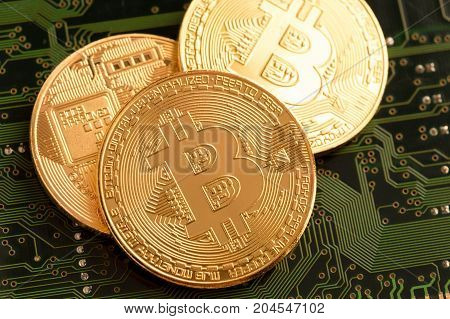 Golden Bitcoin Cryptocurrency On Circuit Board.
