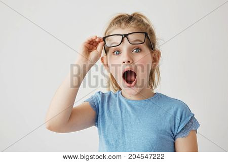 Charming little blonde lady with blue eyes reises glasses with hand in happy excitement of new big bed in her sleeping room as a present