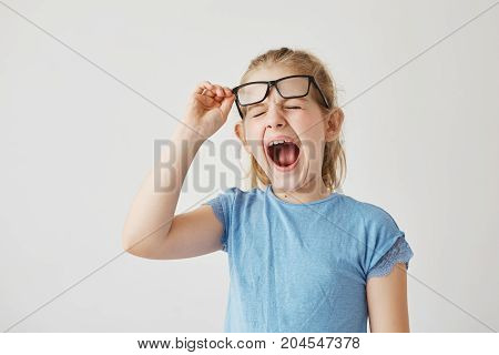 Funny small blonde girl with pretty blue eyes raising glasses and yawning with closed eyes in classroom because long boring lesson