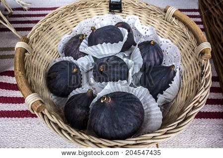 Fresh juicy fig fruits lie in a wicker basket beautifully decorated in white paper napkins. Autumn nature concept.