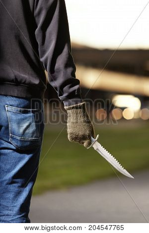 Man armed with combat knife preparing for attack on public