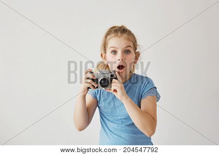 Little blond miss with blue eyes was taking family photo of parents with film camera when dad slipped and fell down. Child looking frightened that parent get hurt