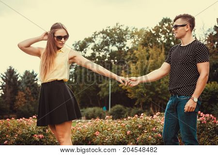 Love romance relationship dating leisure.Youthful couple spending time together. Young girl and boy olding hands in park.