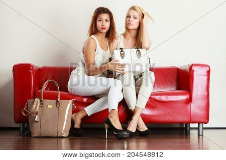 Two Women Sitting On Sofa Presenting Bag