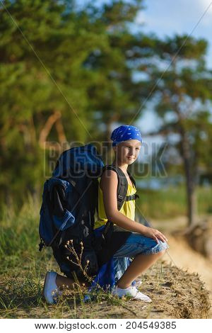 boy with backpack looks into the distance. Adventure, travel, tourism concept.