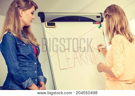 Education knowledge wisdom and learn new things concept - student girls writting Learning word on whiteboard