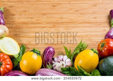 Bamboo plate with copy space restaurant concept with fresh colorful organic vegetables - round courgette small eggplants tomatoes diet concept Italian and French food healthy food. Menu template.
