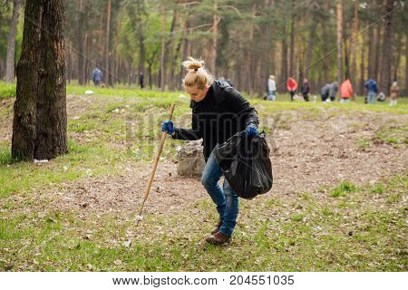 Young blonde girl picking up the garbage and putting it in a black garbage bag on a natural background. Ecology protection concept.