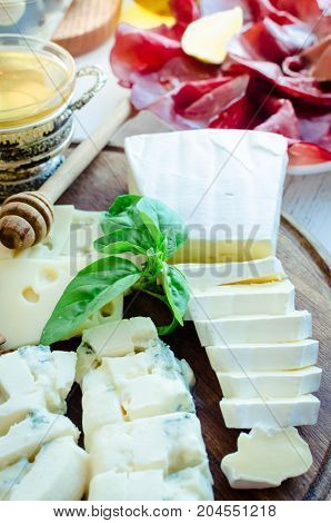 Cheese platter: Brie Parmesan cheddar gouda gorgonzola and other with walnuts and honey on wooden board. Tasty appetizers with different kind of cheese. Delicious snack on party or picnic time.