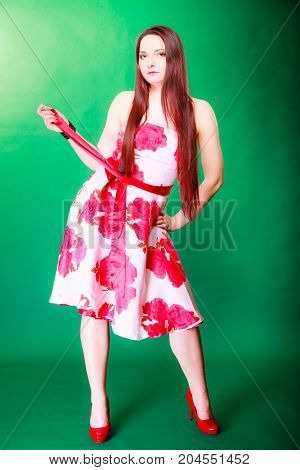 Summertime vacation holiday and date concept. Young long haired woman in floral outfit red high heels on green background in studio.