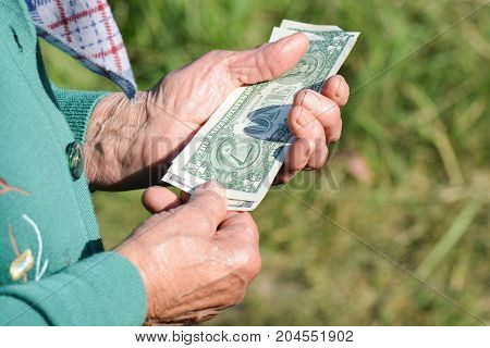 The old woman is holding money in her hands. An elderly woman with dollars in her hands. Poverty alms.