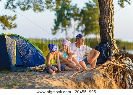 Happy family with backpack and tent looks into the distance.