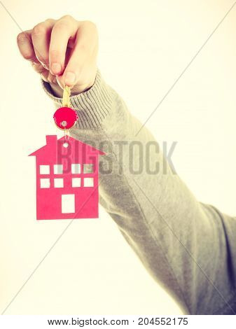 Household ownership security real estate symbolism concept. Key ring with house pendant. Home symbol held by human hand.