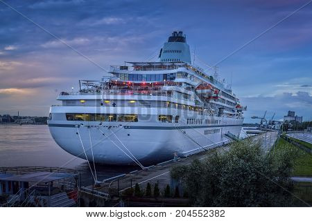 Beautiful white luxury cruise ship on stay at Riga harbor during sunset