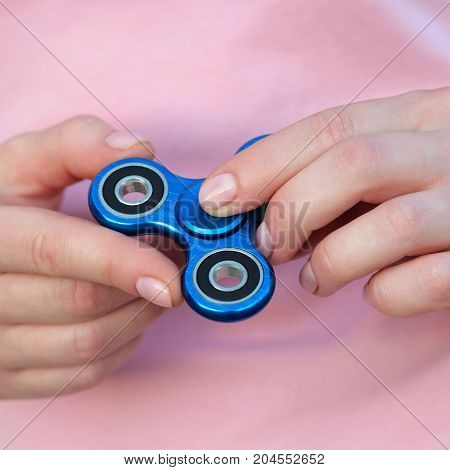 girl in pink t-shirt is playing blue metal spinner in hands on the street woman playing with a popular fidget spinner toy anxiety relief toy anti stress and relaxation fidgets