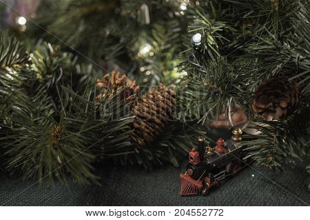 Christmas decor background with toy train and pine cones surrounded by greenery