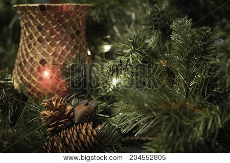 Christmas decor background with red candle holder, pine cones and mouse surrounded by greenery