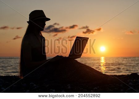 Girl In A Hat Sitting And Working At His Laptop Against The Sea At Sunset. Silhouette