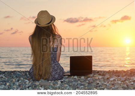 Girl In A Hat Sits On The Beach, Near A Laptop. Sea At Sunset