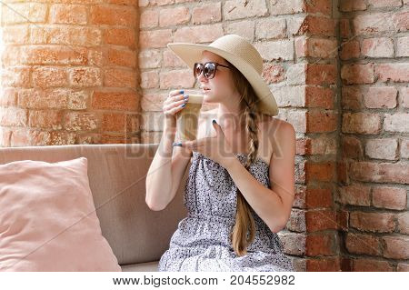 Girl In A Hat And Sunglasses Drinks Latte In A Street Cafe. Travel And Leisure
