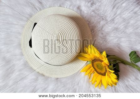 Straw Hat With Ribbon And Sunflower On White Fur. Fashionable Concept, Top View