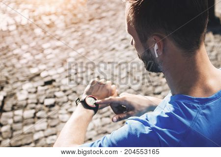 Young bearded athlete with bluetooth headphones analyzes result of training on smartwatch. Concept of modern athlete with smart watch and gadgets in urban environment