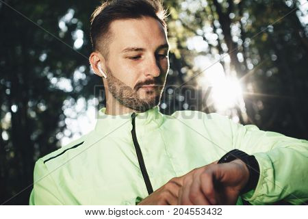 Trendy Sportsman Looks At Smartwatch And Learns Results Of Training And Jogging In Forest. Bright Su
