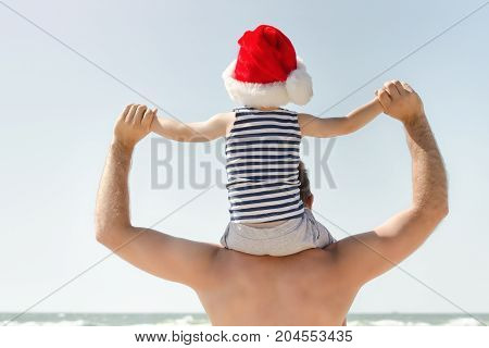 Kid In Santa Hat Sitting On His Father's Shoulders. Sea Shore. Back View