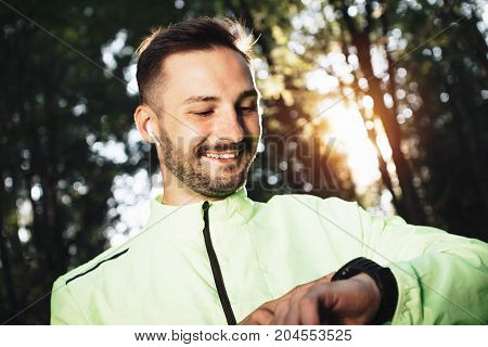 Athlete In Sportswear And Wireless Bluetooth Headphones Looks At Smart Watch On His Arm And Rejoices