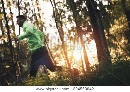 Athlete Is Engaged In Cross-country Running In Outdoors In Forest. Specially Blurred Sportsman. Inte