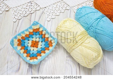 Crochet handmade granny square and yarn balls. The beginning of bright plaid blanket. Colorful knitted handmade work. Homemade creative crochet lace pattern with crochet stitches. Rustic background