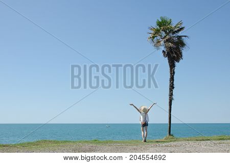 Beautiful Girl Stands With Her Back On A Background Of High Palm. Hands Up. Sea And Blue Sky