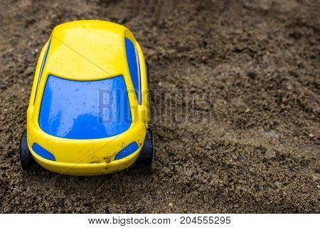 Toy yellow passenger car with blue glass in the sand toy for the street
