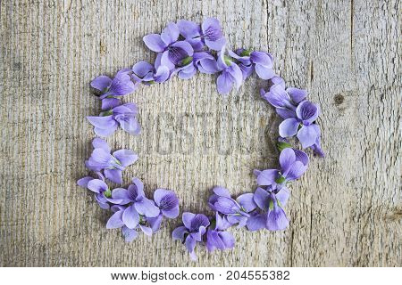 Beautiful light purple flower lined circle on a light wooden background layout blank