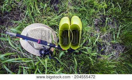 Rubber boots hat and rod on the grass. Set for fishing.