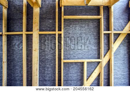 Framework of the house wall of boards and timber a window a vapor barrier from the inside
