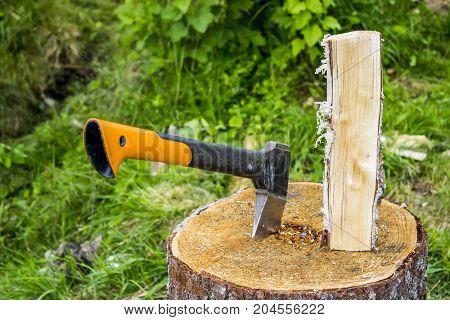 An ax in a stump a birch log in the garden