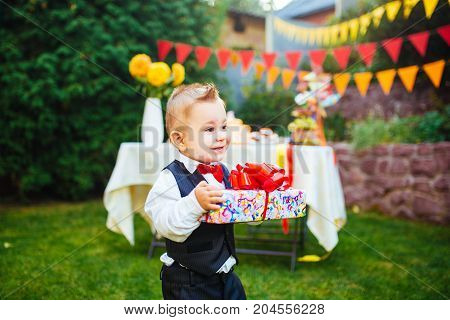 Surprise For The Birthday. The Boy Is Holding A Box With A Gift In The Yard On The Background Of A F