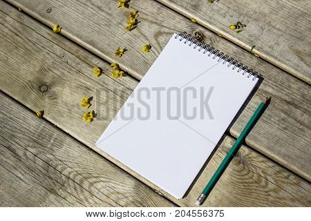 Blank Sheet Of Notepad, Pencil, On A Wooden Old Table, Yellow Flowers, Top View