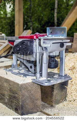 The hand power tool is a plane. Sawdust the process of the carpenter's work as a builder when building a frame house