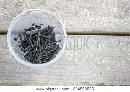 Plastic bucket with long screws on a background of wooden boards and sawdust.