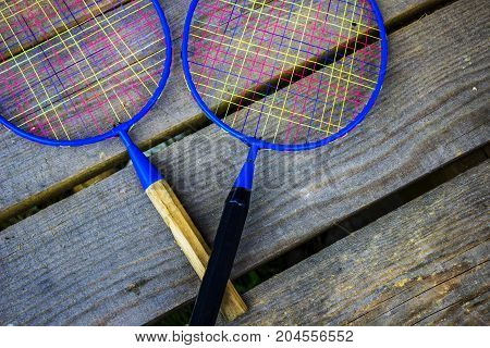 Racquets for badminton with short arms and colored nets. Different grips. Active sports game.