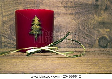 Christmas New Year red wax candle with a Christmas tree pattern on a dark wooden background
