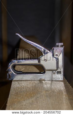 A building stapler on the boards. Construction of a frame house. Hand tool