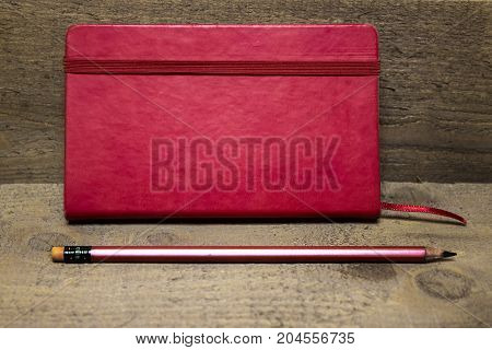 Red diary closed red pencil on a dark brown wooden background