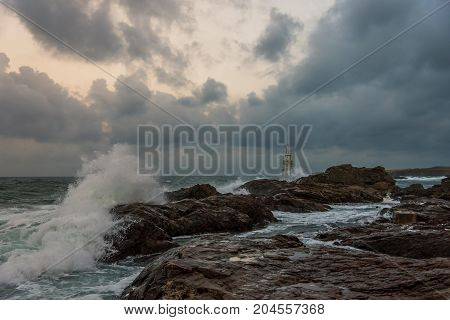 Stormy cloudy day. Dramatic sky and huge waves at the Lighthouse Ahtopol Bulgaria