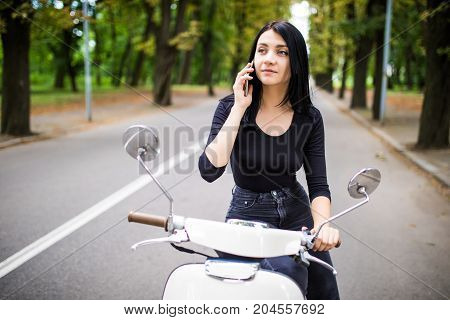 Beautiful young woman dressed casual sitting on scooter and talking on phone. Girl sitting on the bike and using Cellular smartphone