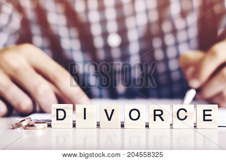 The Concept Of Divorce. The Word - Divorce Rings In The Foreground, A Young Man In A Plaid Shirt Sig