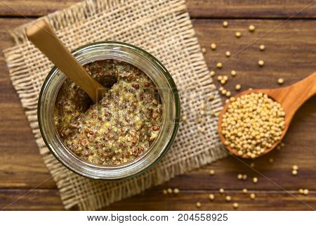 Whole grain mustard in glass jar photographed overhead on wood natural light (Selective Focus Focus on the top of the mustard)